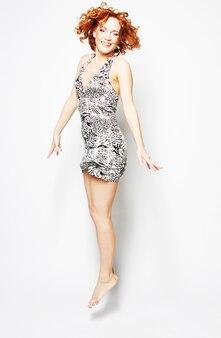 Молодая очаровательная женщина в платье прыгает по белой поверхности