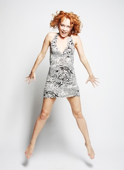 Молодая очаровательная женщина в платье прыжки