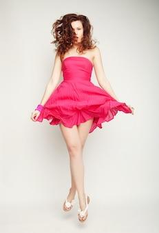 Молодая очаровательная женщина в розовом платье прыгает