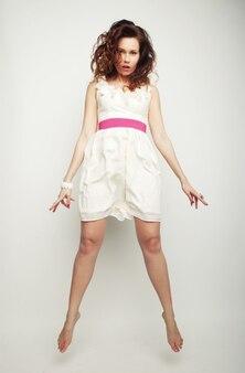 灰色の背景を飛び越えて白いドレスの若い魅力的な女性
