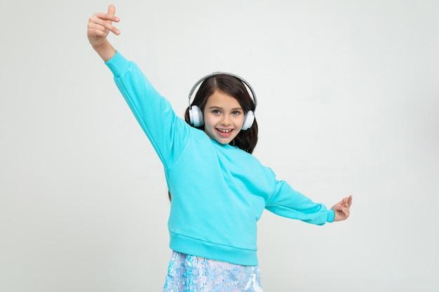 Юная очаровательная девушка в бирюзовой блузке с большими наушниками увлекается музыкой и танцами