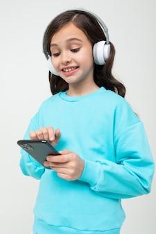 Молодая обаятельная девушка в бирюзовой блузке с большими наушниками выбирает песню из плейлиста по телефону в студии