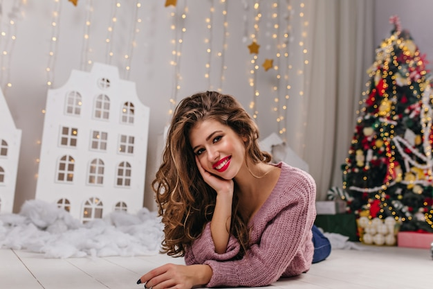 Young charming girl lying on  white carpet and posing against christmas tree