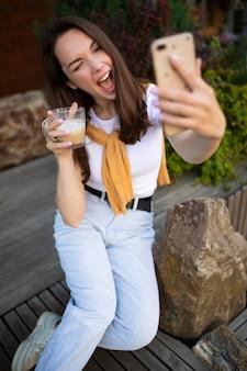 매력적인 소녀는 여름 녹색 공원에 앉아있는 동안 전화 셀카를 만듭니다.