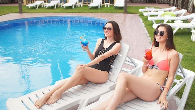 若い魅力的な女の子は、プール近くのガンダーで休んでカクテルを楽しみます。