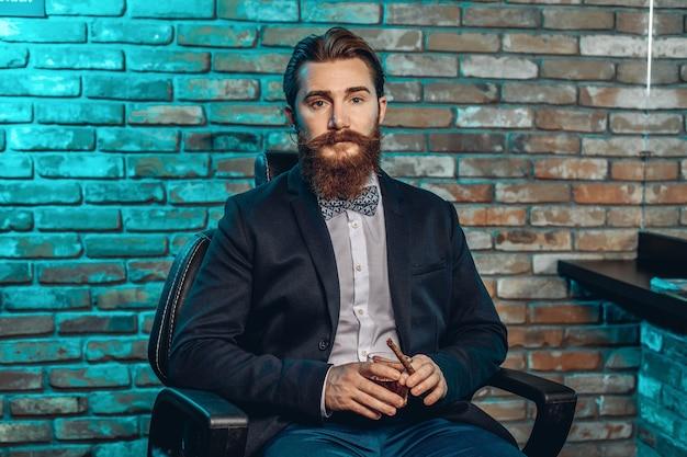 Молодой очаровательный мужчина в костюме сидит на сиденье и держит в руках стакан виски и сигару. концепция пафоса