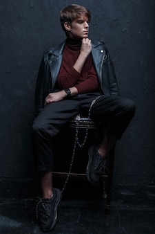 Young charming man with a hairstyle in a retro-style jacket in red golf in stylish jeans in black sneakers with a silver metal chain sits and poses on a wooden chair in a dark studio. stylish guy