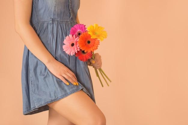 カジュアルなジーンズの服を着た若い魅力的な笑顔の女の子。カラフルな生花ガーベラとデニムドレスの若い素敵な女の子