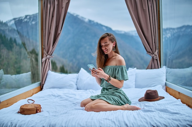 Молодая очаровательная улыбающаяся красивая бохо шикарная брюнетка женщина-путешественница в изумрудном платье с открытыми плечами сидит на кровати в гостиничном номере с видом на горы и использует телефон для онлайн-общения