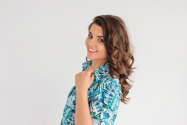 Молодая очаровательная улыбающаяся брюнетка с волнистыми волосами в летнем платье, изолировать на белом