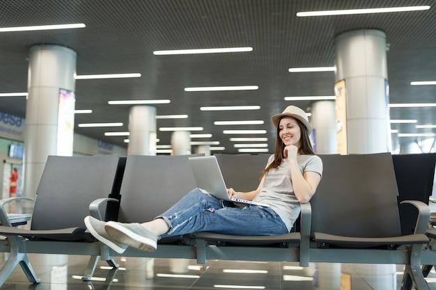 Молодой очаровательный путешественник турист женщина в шляпе работает на ноутбуке во время ожидания в холле вестибюля в международном аэропорту