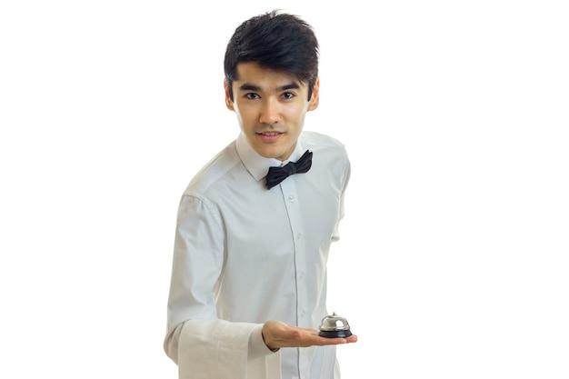 흰 셔츠에 젊은 매력적인 웨이터는 앞으로 흰 벽에 고립 기댈