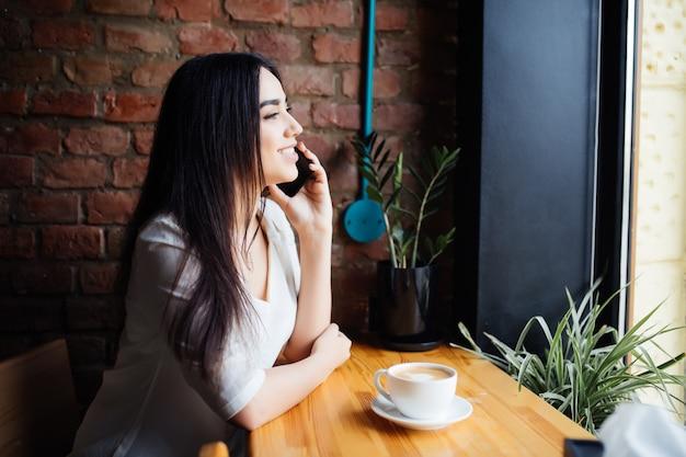 커피 숍에 혼자 앉아있는 동안 휴대 전화로 전화하는 젊은 매력적인 여자