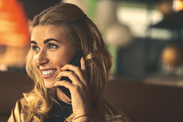 携帯電話で呼び出す若い魅力的な女性