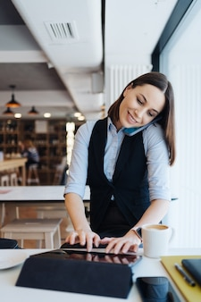 Young charming woman calling with smartphone while sitting alone in coffee shop, having talking conversation with mobile phone
