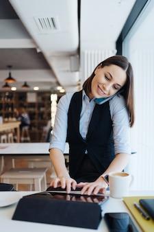 コーヒーショップで一人で座って、携帯電話で会話をしながらスマートフォンで呼び出す若い魅力的な女性