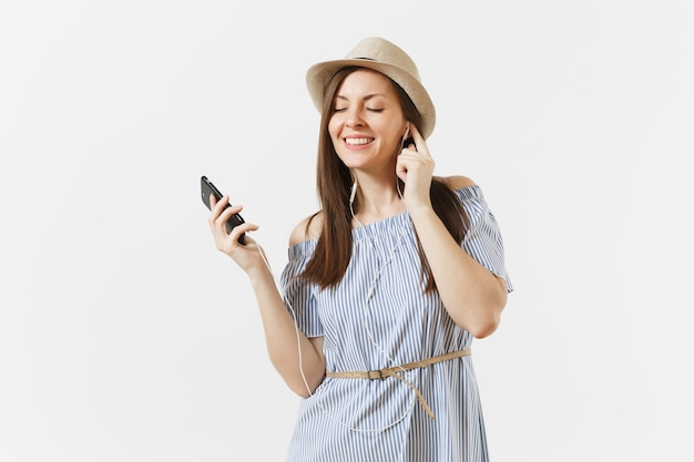 Young charming woman in dress, hat listening music in earphones on mobile phone, enjoy, relax isolated on white background. people, sincere emotions, lifestyle concept. advertising area. copy space.