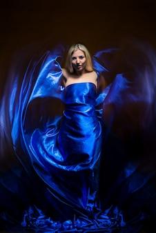 푸른 안개 가운데 어둠 속에서 포즈를 취하는 파란 드레스에 젊은 매력적인 여자 여신. 신비주의와 수수께끼의 개념. 여성 마법 개념