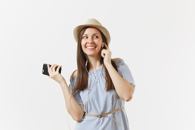 Молодая очаровательная женщина в платье, шляпе, слушая музыку в наушниках на мобильном телефоне, наслаждайтесь, расслабляйтесь на белом фоне. люди, искренние эмоции, концепция образа жизни. рекламная площадка. скопируйте пространство.