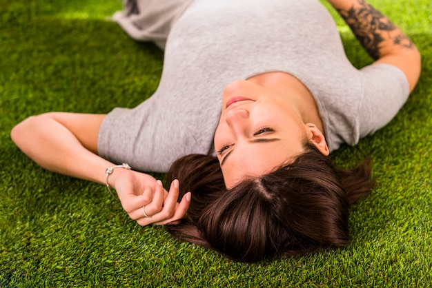 Young charming woman lying on lawn