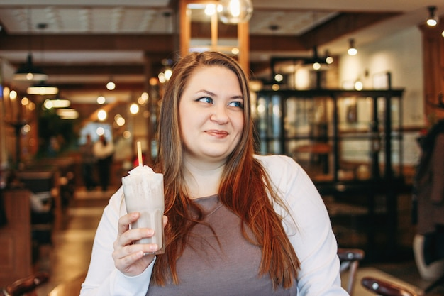 Young charming woman plus size with milkshake in hand in cafe, enjoing life and appearance