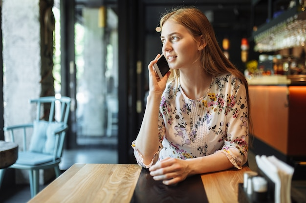Young charming woman talking on the phone sitting alone in the cafe in her spare time, attractive woman with a cute smile having a conversation with a mobile phone while relaxing in the cafe