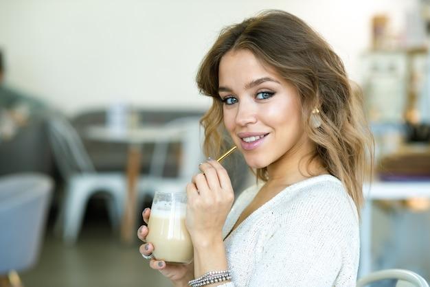 休憩中に居心地の良いカフェでカプチーノのグラスを持っている間あなたを見ているブロンドの髪を持つ若い魅力的な女性