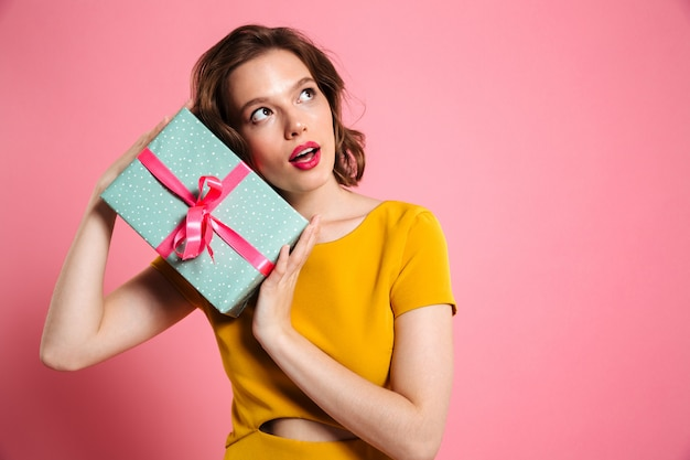 Young charming woman in yellow dress holding gift box, looking aside