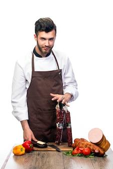 Молодой повар с разными видами салями на столе, реклама колбасного отдела