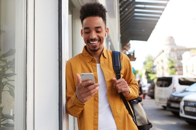 Il giovane ragazzo afroamericano allegro in camicia gialla, cammina per strada e tiene il telefono, ha ricevuto un messaggio con un video divertente, sembra gioioso e ampiamente sorridente.