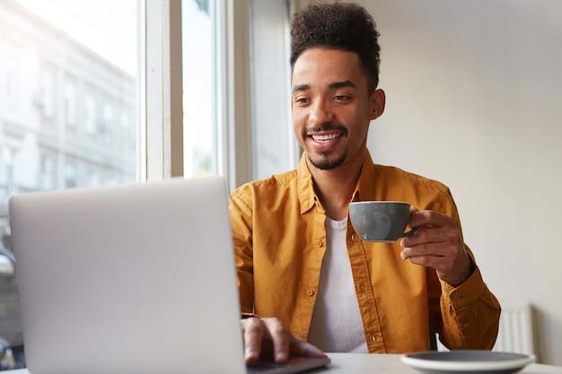 Il giovane uomo sorridente afroamericano allegro, si siede in un caffè, lavora a un laptop e chiacchiera con il suo capo, si diverte a lavorare come freelance, beve caffè aromatico.
