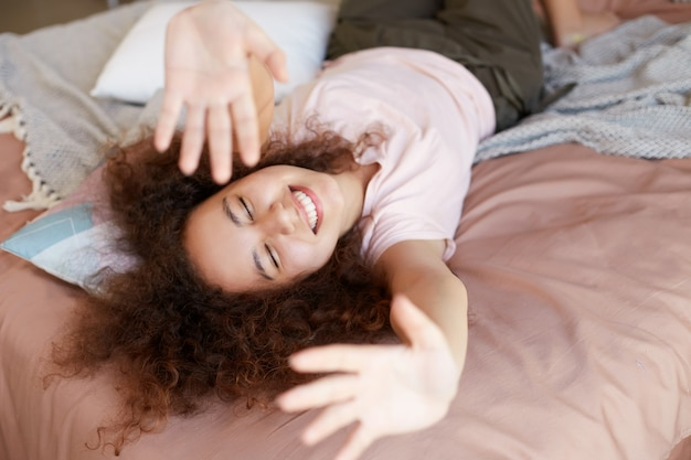 La giovane donna afroamericana allegra si gode la giornata di sole a casa, trascorre la giornata libera e riposa a casa, sdraiata sul letto e ampiamente sorridente con gli occhi chiusi e le mani in alto.