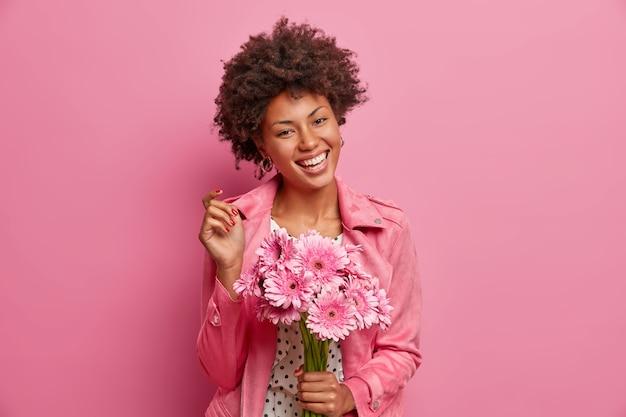 Giovane donna afroamericana allegra con trucco naturale, ampio sorriso, tiene un mazzo di fiori, va a congratularsi con un amico, gode di un piacevole odore di gerbere