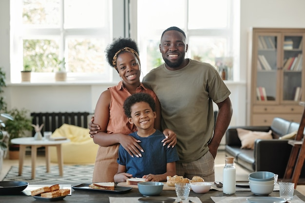 Young cheerful african family consisting of mother, father and cute little son standing by kitchen table in front of camera in home environment