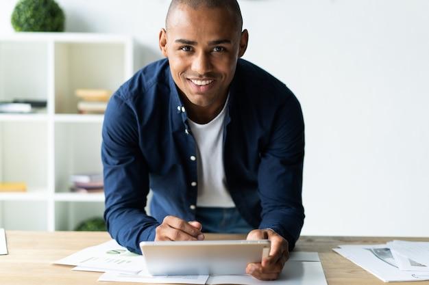 Молодой веселый африканский мужчина держит цифровой планшет и с улыбкой смотрит в камеру, стоя на своем рабочем месте