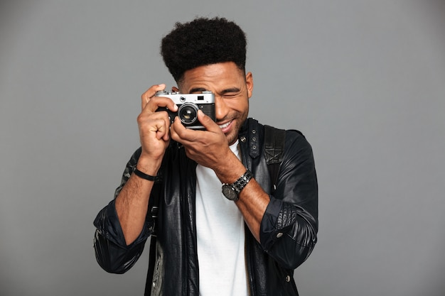 Young cheerful african man looking through retro cameras objective while taking photo