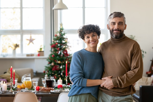 Молодая веселая и ласковая пара в повседневной одежде смотрит на вас с улыбками на фоне сервированного праздничного стола, приготовленного для семейного рождественского ужина
