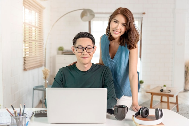 Young cheerful asian couple colleagues work with laptop computer indoors in office talking with each other.