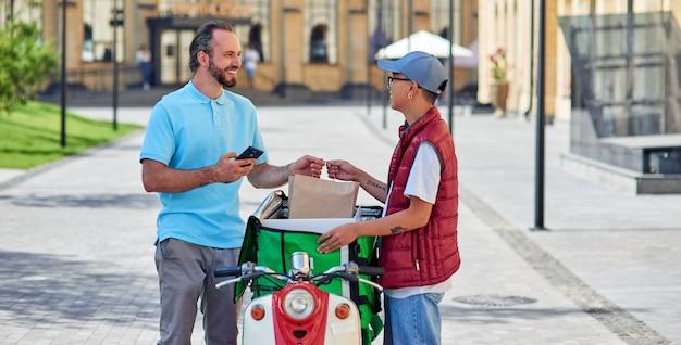 스쿠터 서 있는 고객에게 음식을 배달하는 보온 가방을 든 젊고 쾌활한 아시아 택배