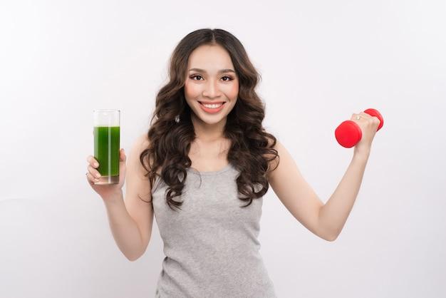 ダンベルと野菜の飲み物を持っている若い陽気なアジアの女性。