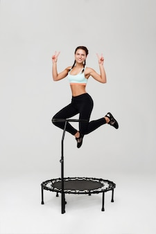 Young cheerful athlete jumping on rebounder smiling isolated on grey