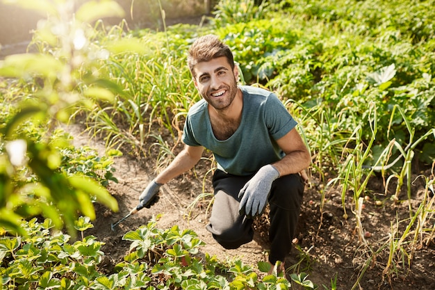 Giovane giardiniere maschio barbuto attraente allegro in maglietta blu e pantaloni sportivi neri sorridente, lavorando in giardino, piantando germogli con la pala.