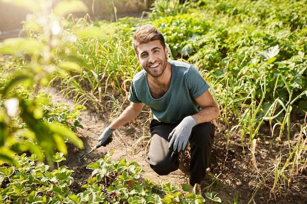 Молодой веселый привлекательный бородатый садовник в синей футболке и черных спортивных штанах улыбается, работает в саду, сажает лопатой ростки.