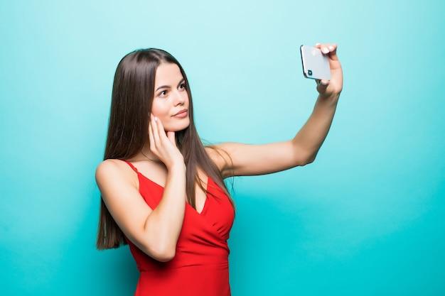 若い陽気な魅力的なブルネットは青い壁に笑っています。彼女はカジュアルな夏服と帽子をかぶって、携帯電話で自分撮りをしています