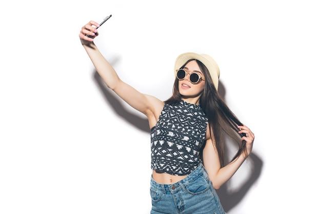若い陽気な魅力的なブルネットの女性は彼女の電話でselfieを取って、カジュアルな夏の服と帽子を着て白い壁に笑みを浮かべてください。