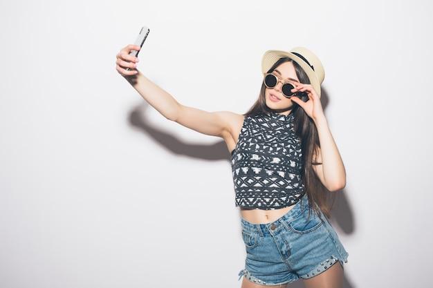若い陽気な魅力的なブルネットの女性は白い壁に電話でselfieを取って、カジュアルな夏の服装と帽子を着て笑っています。