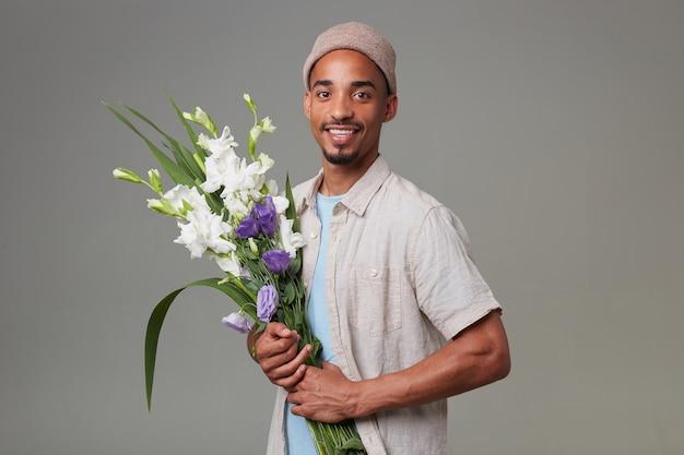 灰色の帽子をかぶった若い陽気な魅力的な男は、彼の花束を持ってポーズをとり、嬉しい表情と笑顔でカメラを見て、灰色の背景の上に立っています。