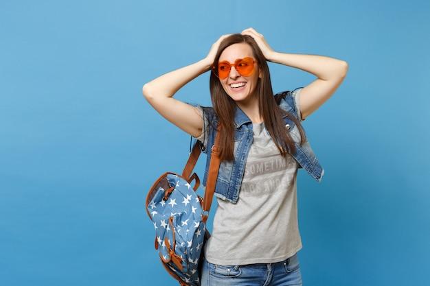 青い背景で隔離の頭に手を置いて脇を見てオレンジ色のハートのメガネのバックパックを持つ若い陽気な魅力的な女性の学生。大学での教育。広告用のスペースをコピーします。