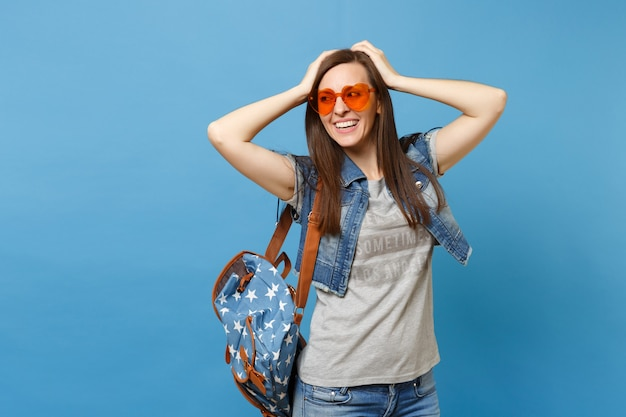 Young cheerful attractive woman student with backpack in orange heart glasses looking aside keeping hands on head isolated on blue background. education in university. copy space for advertisement.