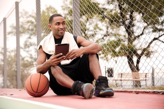 Молодой веселый баскетболист сидит в парке возле баскетбола и держит планшет